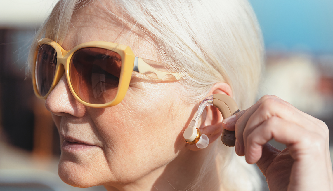 woman wearing sunglasses outdoors, putting on her hearing aid