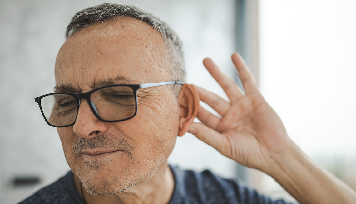man holding his ear, looks stressed about not being able to hear