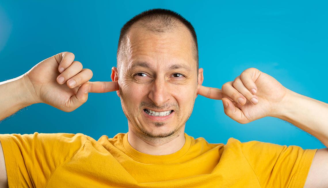 Un hombre se tapa los oídos con sus dedos índices