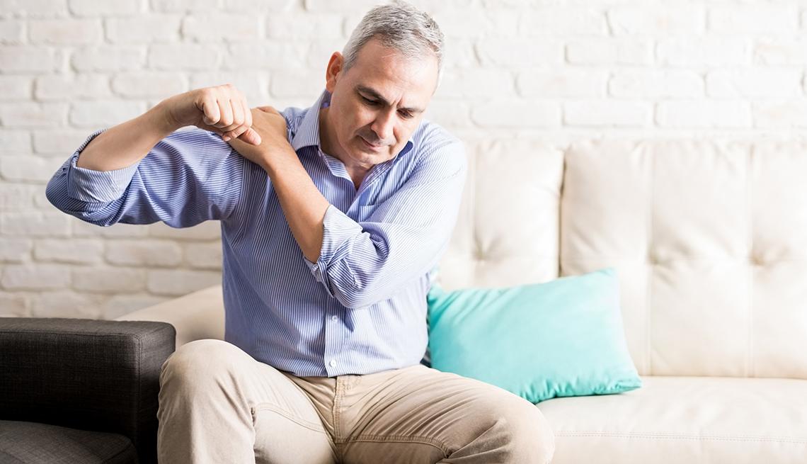 Un hombre, sentado en un sofá, mueve su hombro para aliviar el dolor