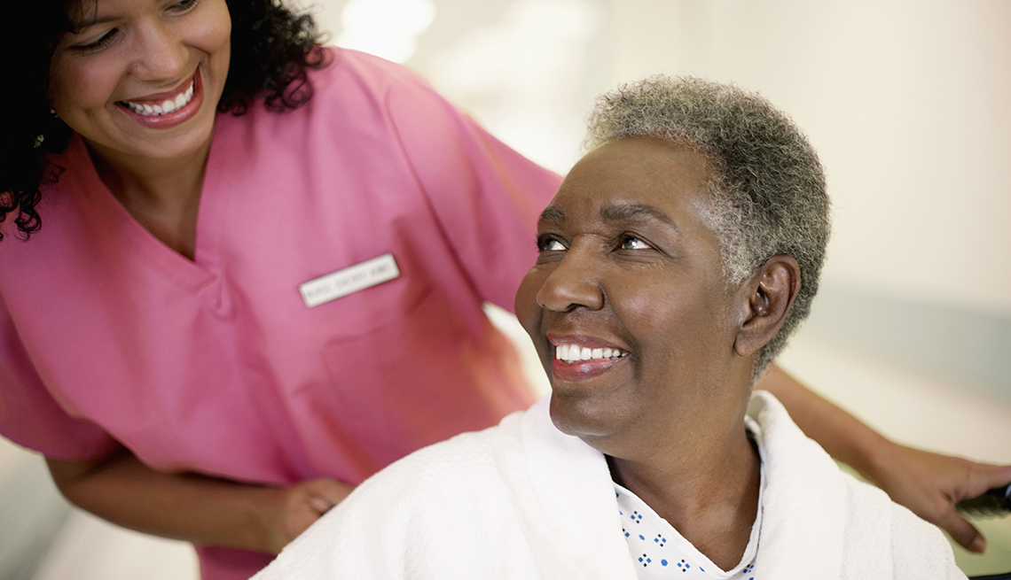 female patient in a wheel chair looking up at her nurse