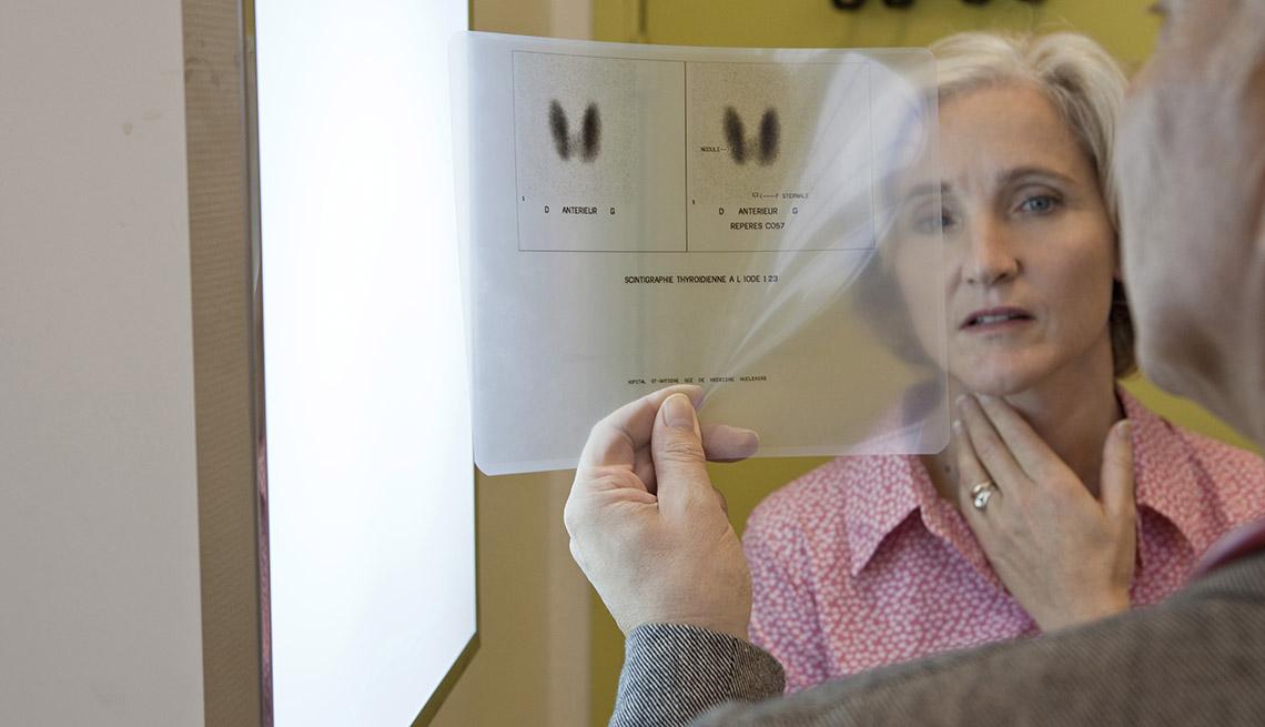 Un médico le muesta una radiografía de su tiroide a una paciente