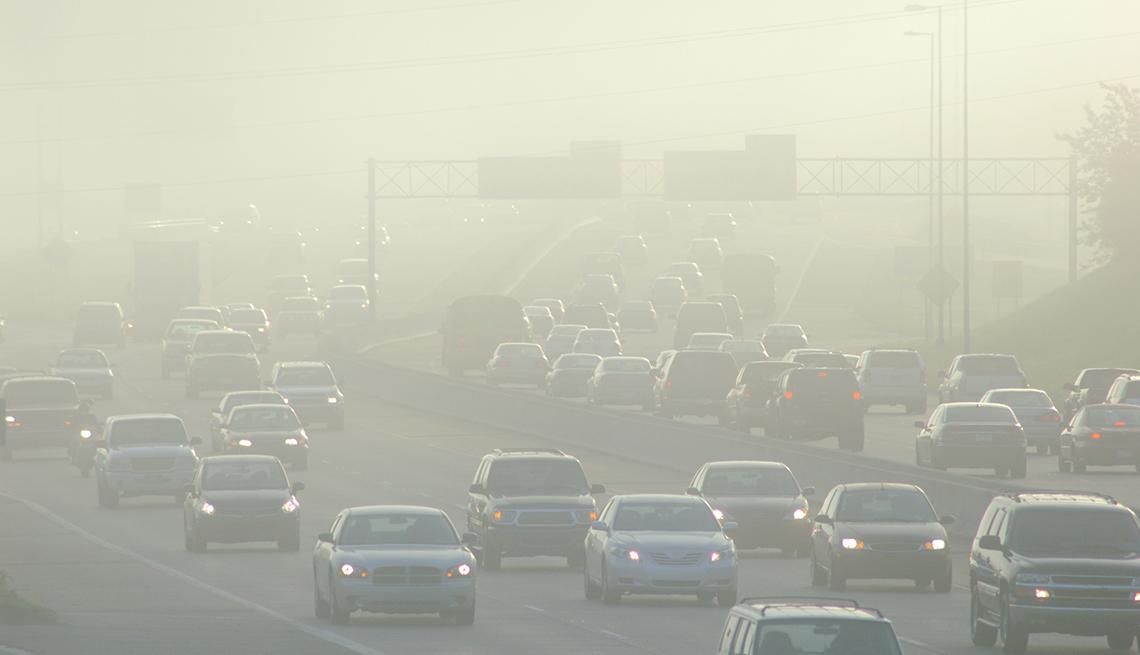 Hora pico de tráfico en una autopisa y niebla
