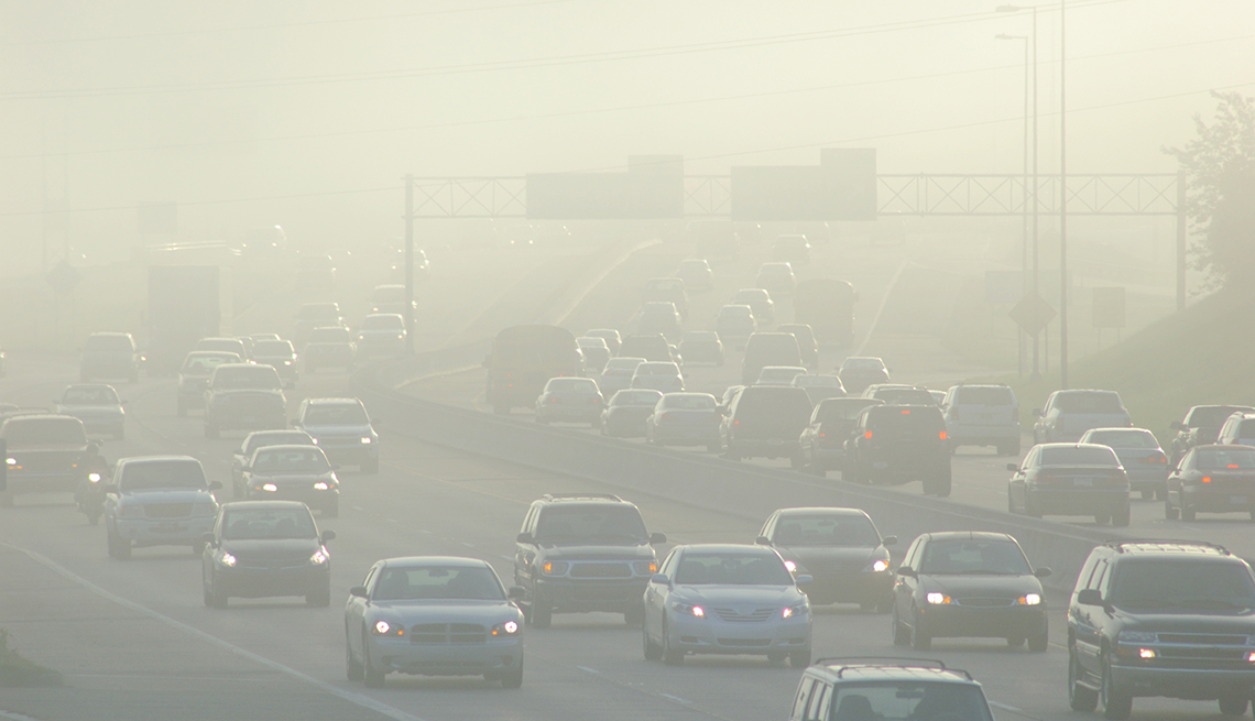 rush hour traffic on highway with smog
