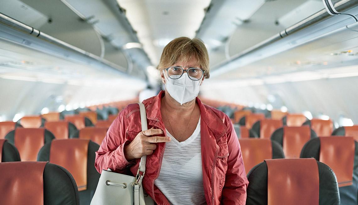 Una mujer, con mascarilla, dentro de un avión