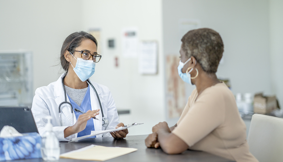 An African American patient talking with her doctor. Both are wearing face masks.