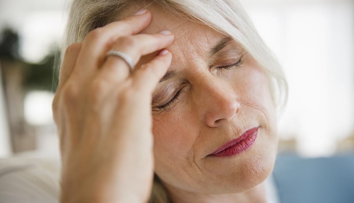 mature blonde woman holding head as if she has a headache