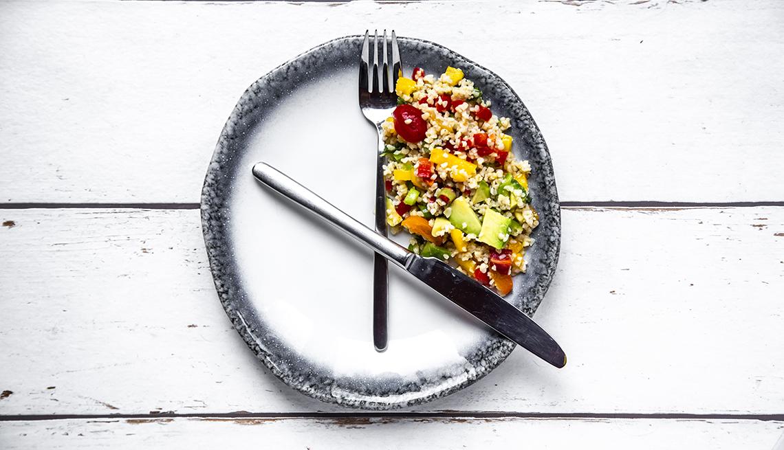 Ensalada en un lado de un plato y los cubiertos simulando un reloj
