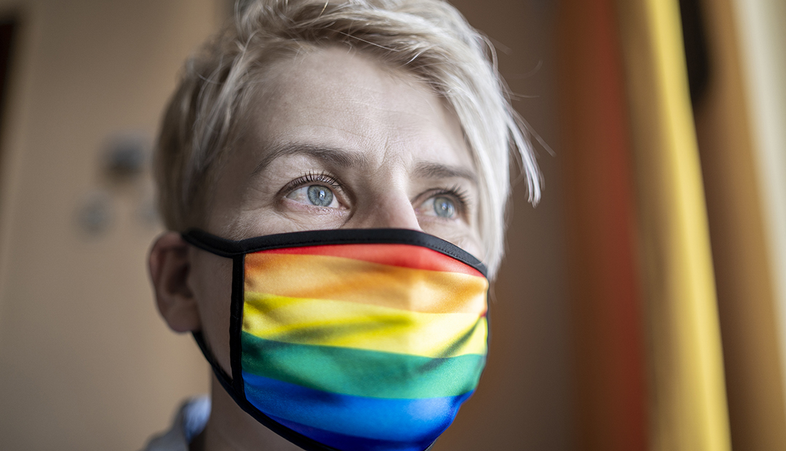 Woman wearing rainbow LGBT pride protective face mask.