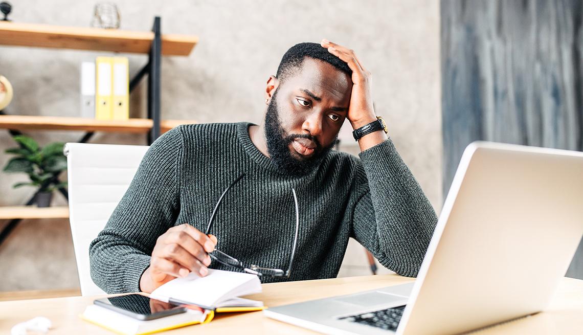 Un hombre, que luce estresado, mira una computadora