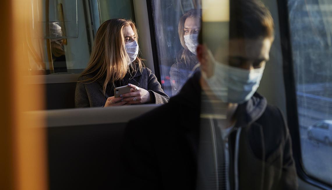 Pasajeros en un autobus usando mascarillas