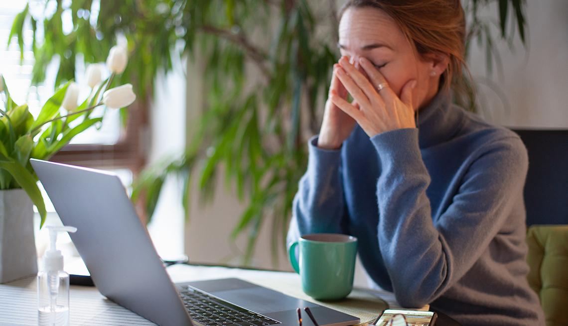 Una mujer sentada frente a su computadora se frota los ojos en señal de cansancio