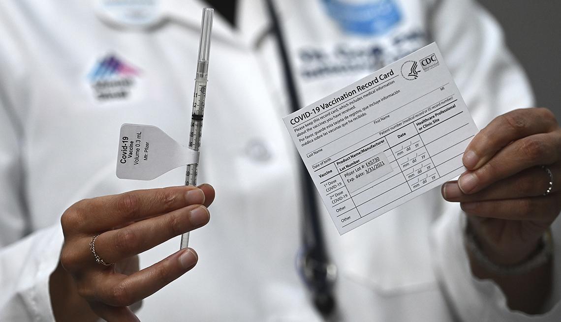 Un médico sostiene una jeringa en una mano y una tarjeta de vacunación contra la COVID-19 en la otra