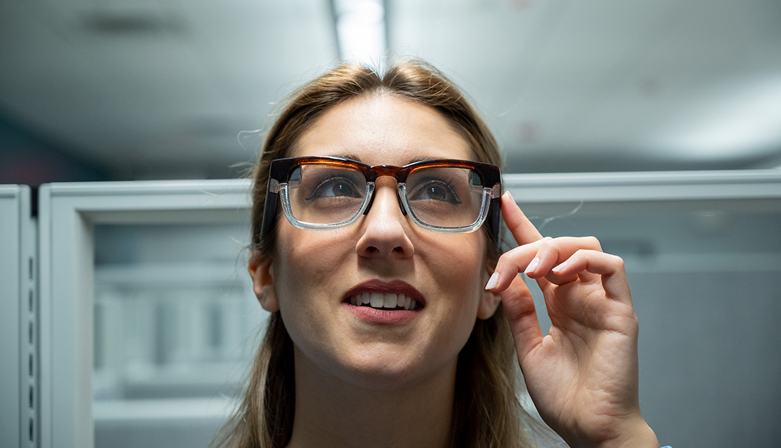 woman tapping the side of her smart glasses