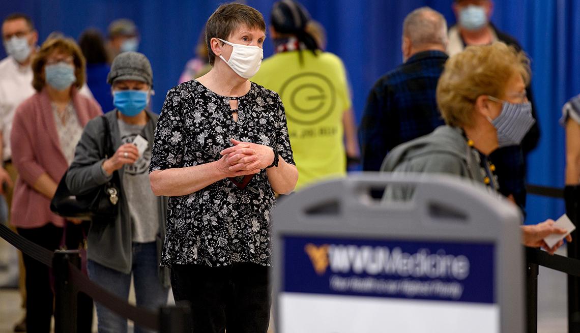 Personas con máscaras protectoras esperan ser vacunados contra la COVID-19