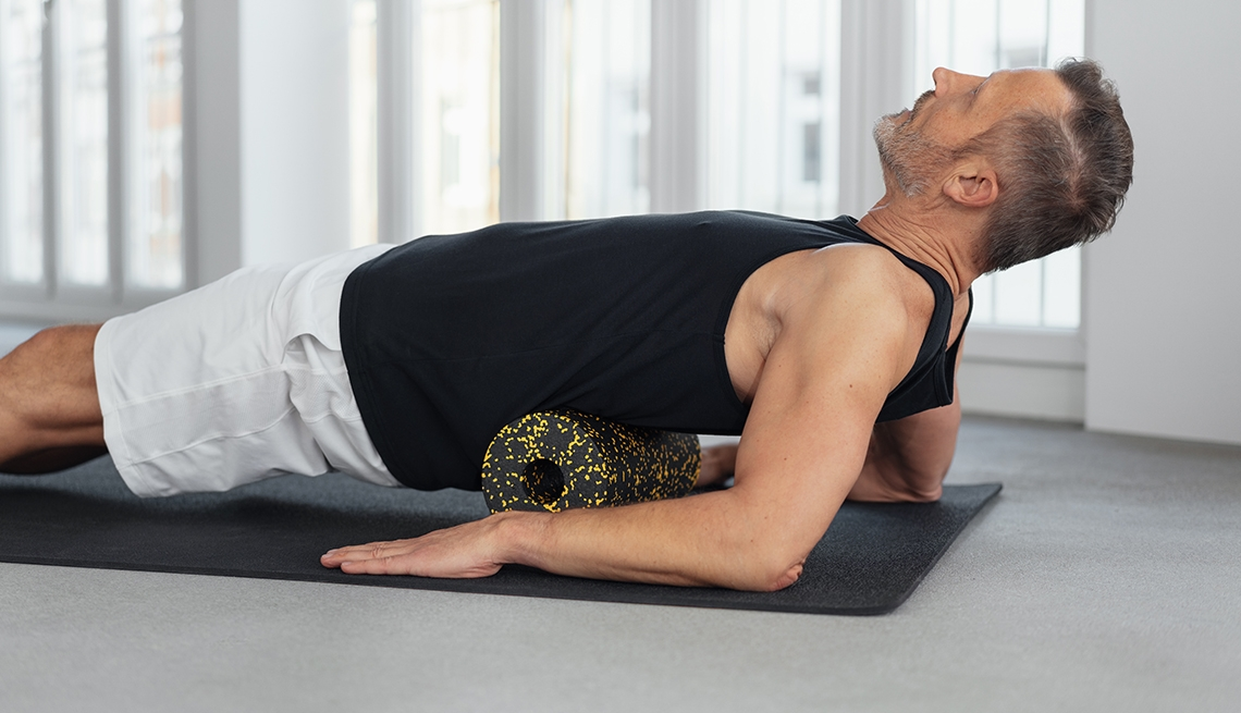 Man using a foam roller to massage his back and spine on a gym mat on the floor