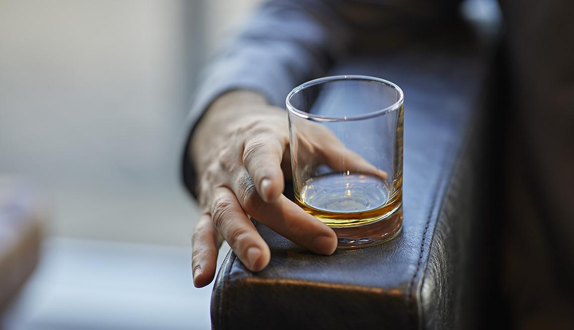 Mano de un hombre en el descanso de una butaca sostiene un vaso con licor