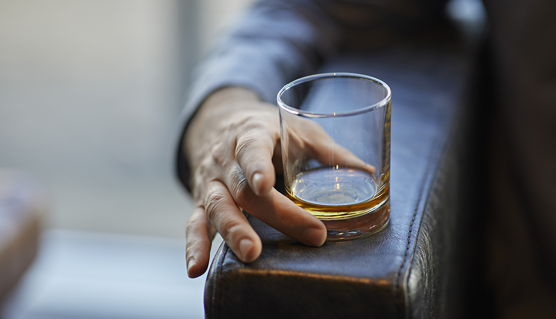man's arm resting on a chair arm holding a glass of alcohol