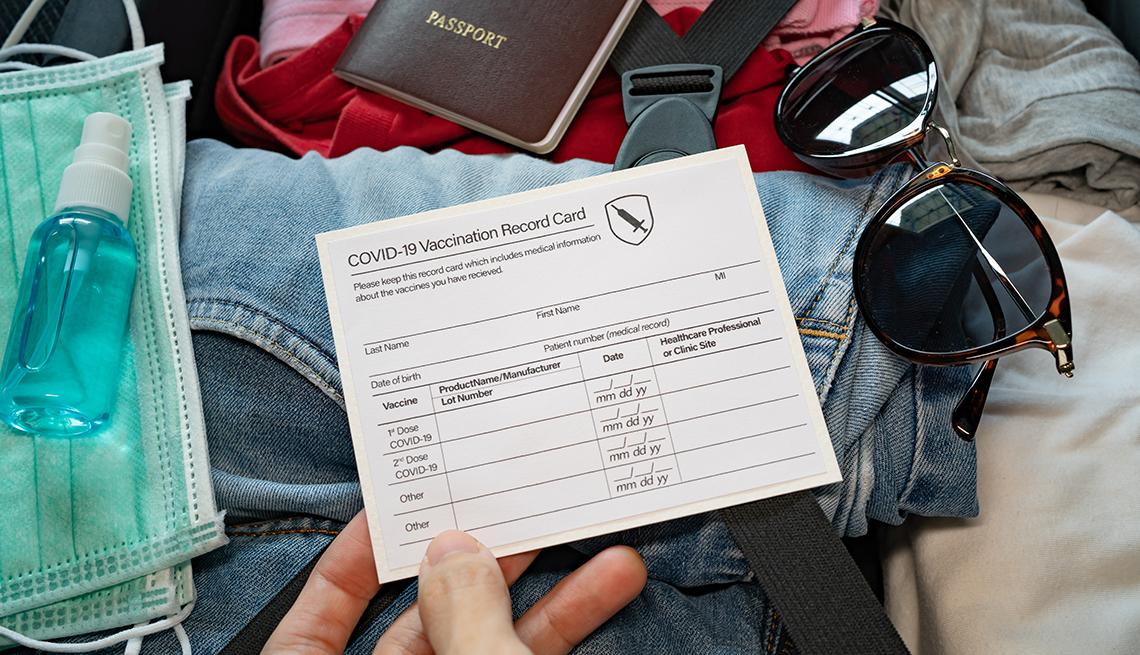 Una mujer coloca su tarjeta de vacunación junto con otros accesorios en una maleta