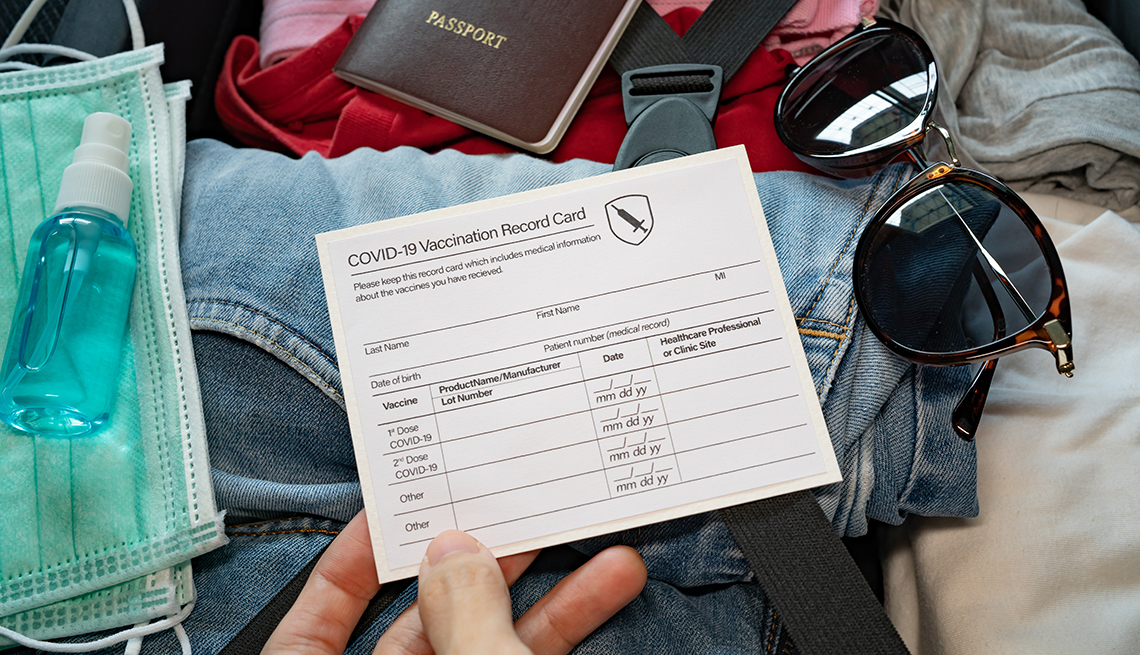 woman's hand holding her COVID vaccination card while packing her suitcase for travel.