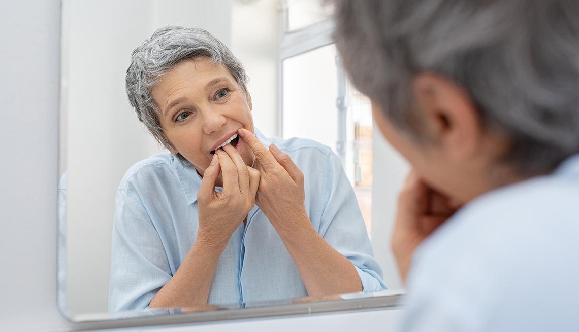 Una mujer limpia sus dientes con hilo dental