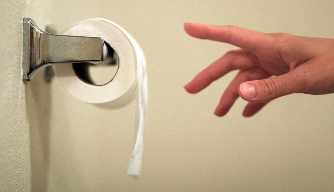 a hand reaching for a piece of toilet paper on a roll dispenser