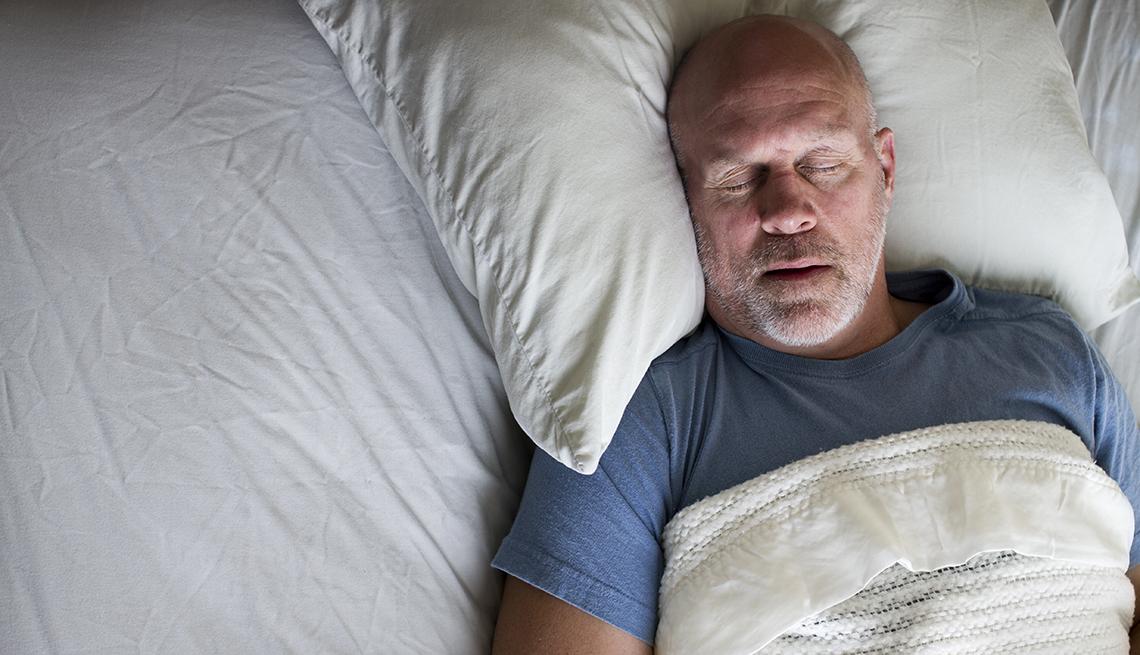 Un hombre duerme en su cama con la boca parcialmente abierta