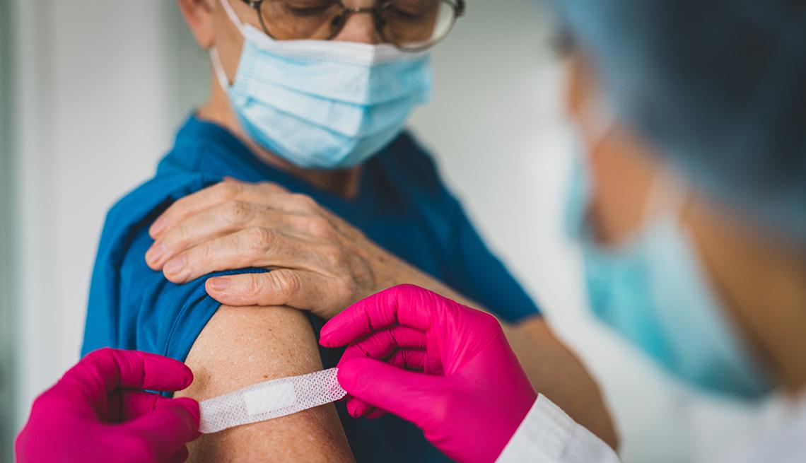 Proveedor médico coloca una tirita en el brazo de un paciente.
