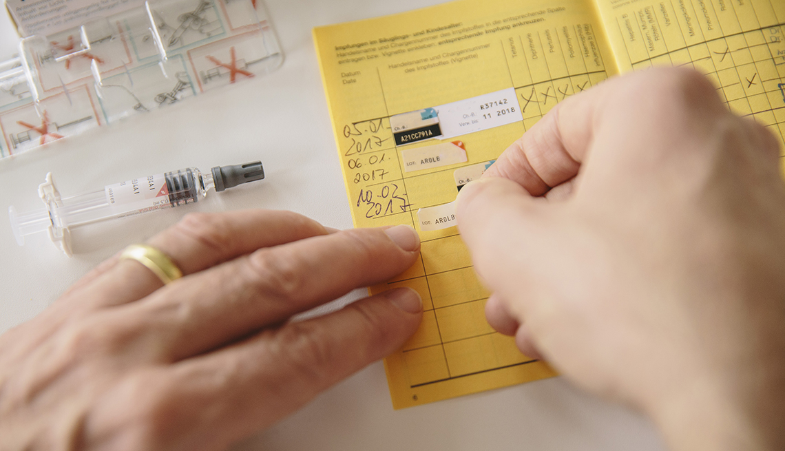 Un doctor agrega información a una tarjeta de vacunas