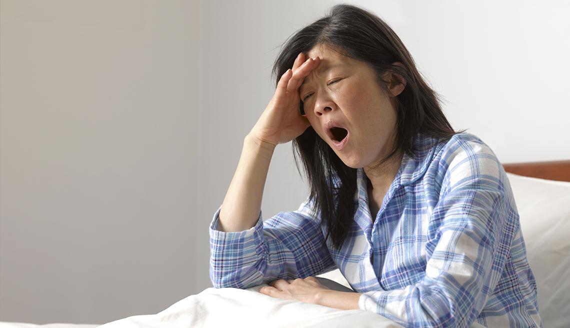 Una mujer bosteza sentada en su cama