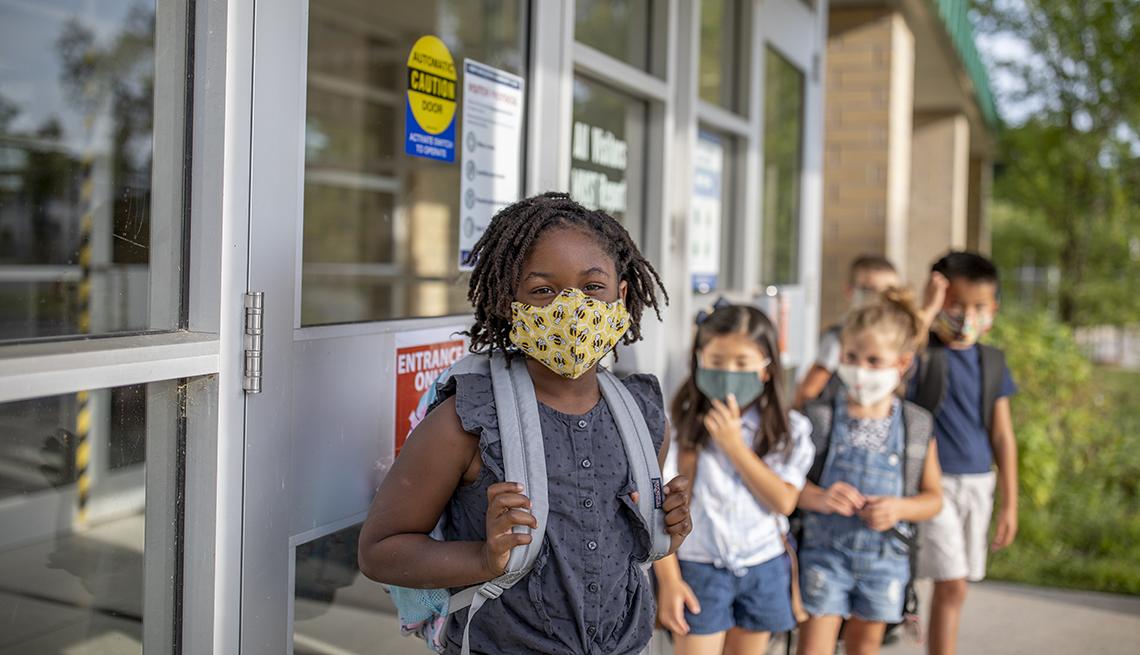 Grupo de niños en fila, cada uno con su mascarilla y listos para entrar a un salón de clases