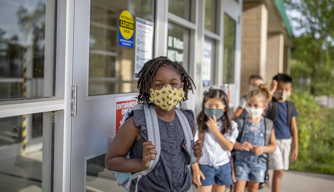 A group of kids stand outside of school with masks on