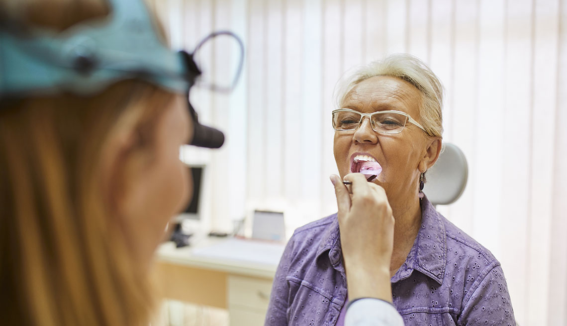 doctor examining female patient's mouth