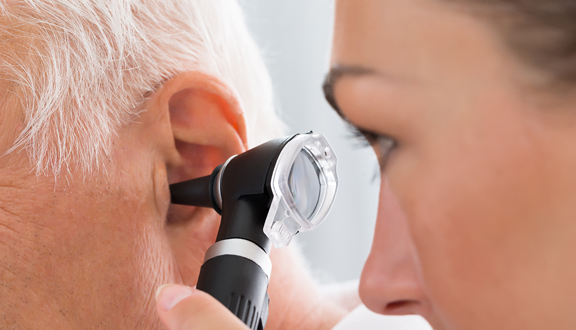 A doctor is looking into a person's ear