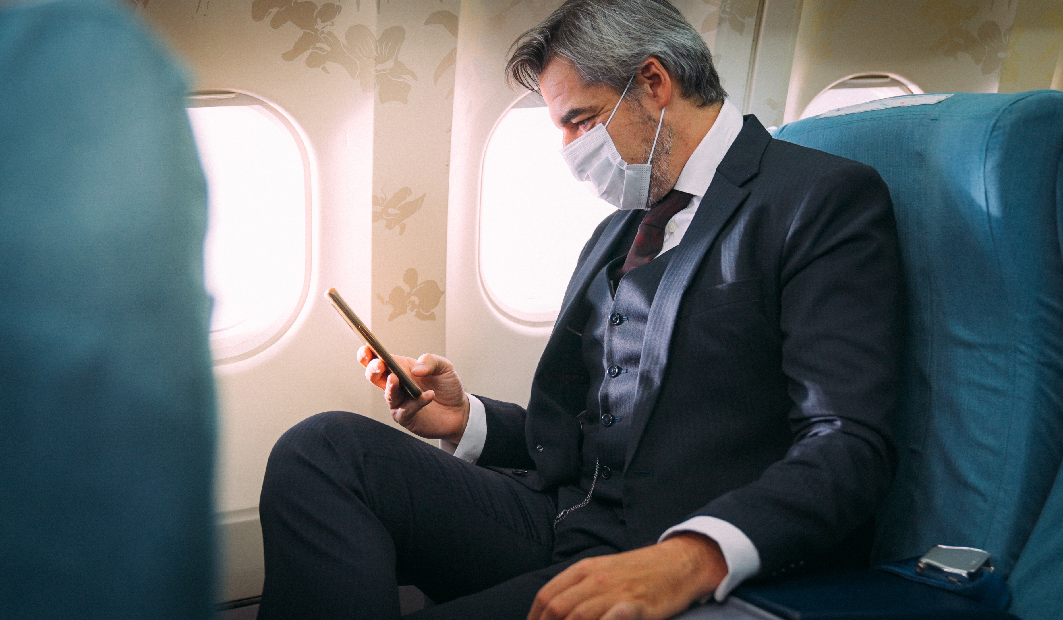 Caucasian businessman wearing protective face mask using smartphone on seat of business class in airplane
