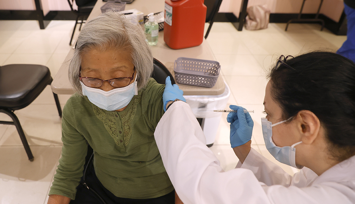 A nurse is giving a woman a vaccine in her arm