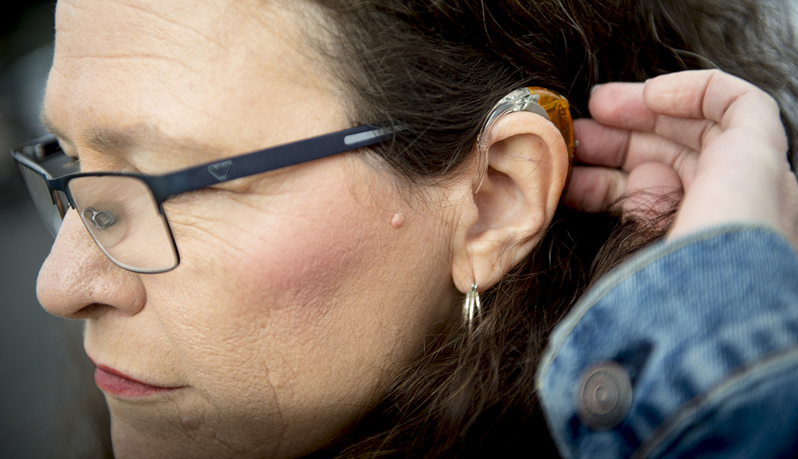 A woman moves her hair away from her ear showing her hearing aid