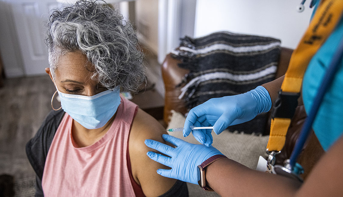 a nurse giving a COVID-19 vaccine to a senior black woman