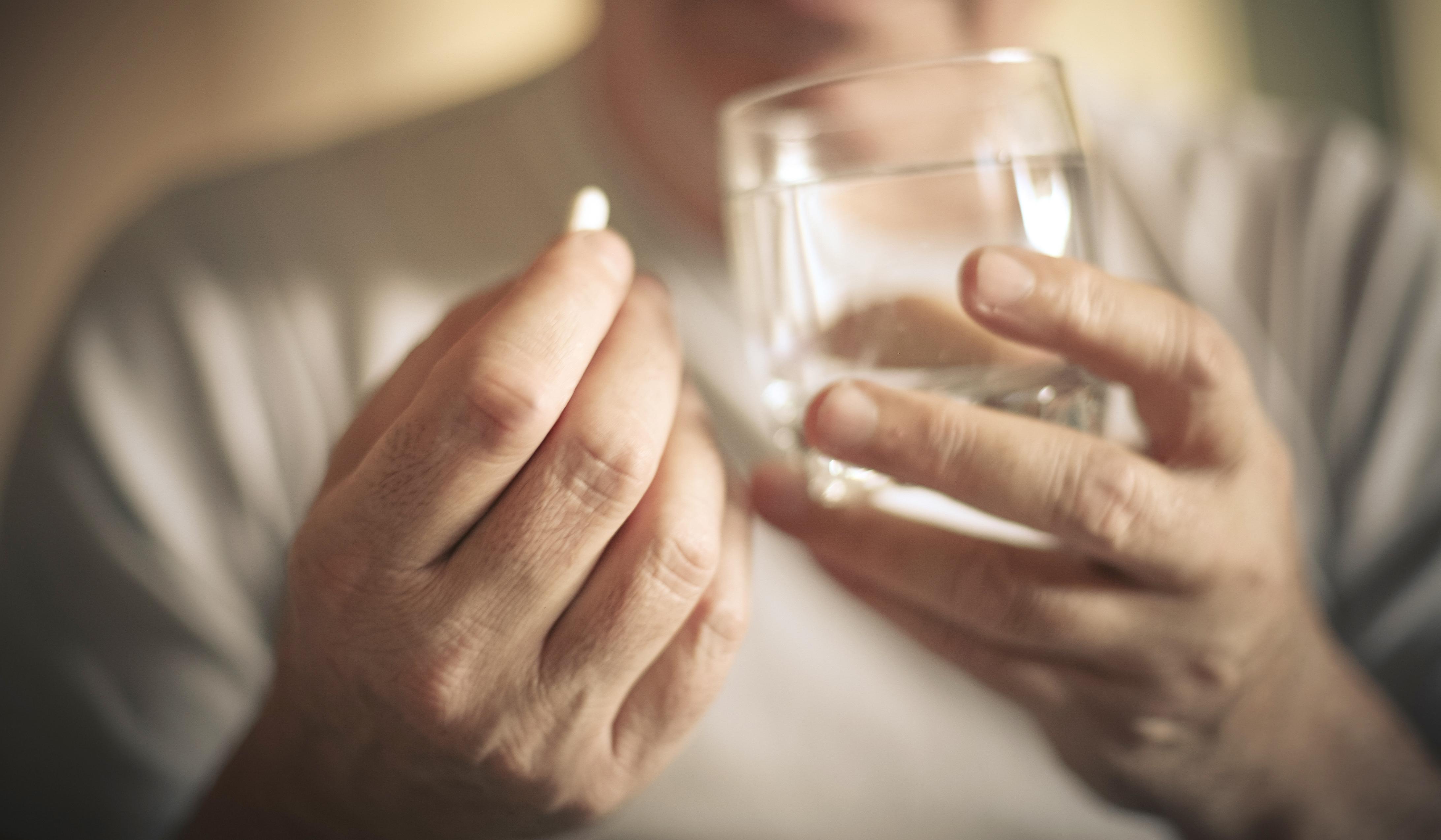 Una persona mayor tomando un medicamento