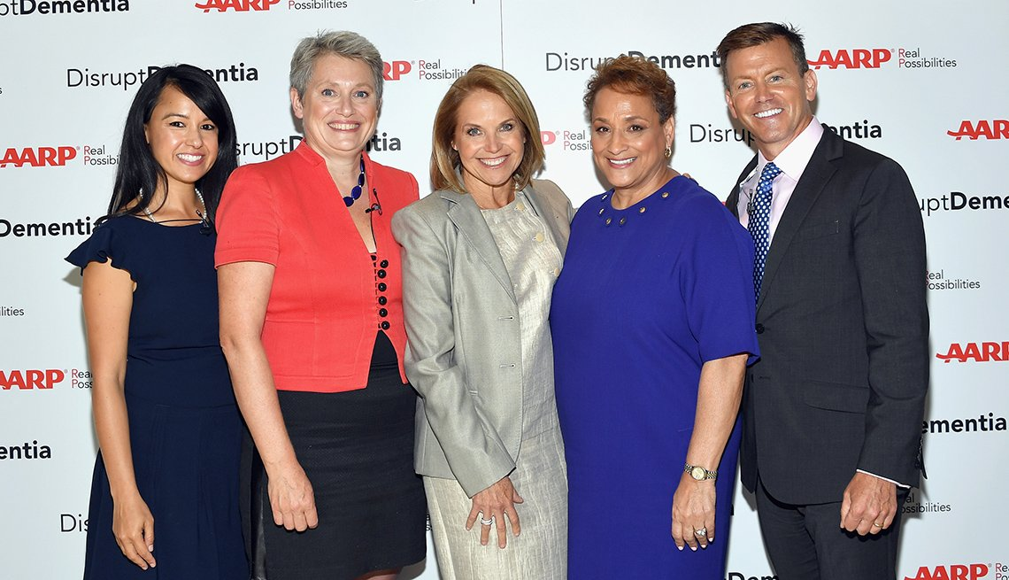 Four women and one man stand in front of a background that says AARP: Disrupt Dementia.