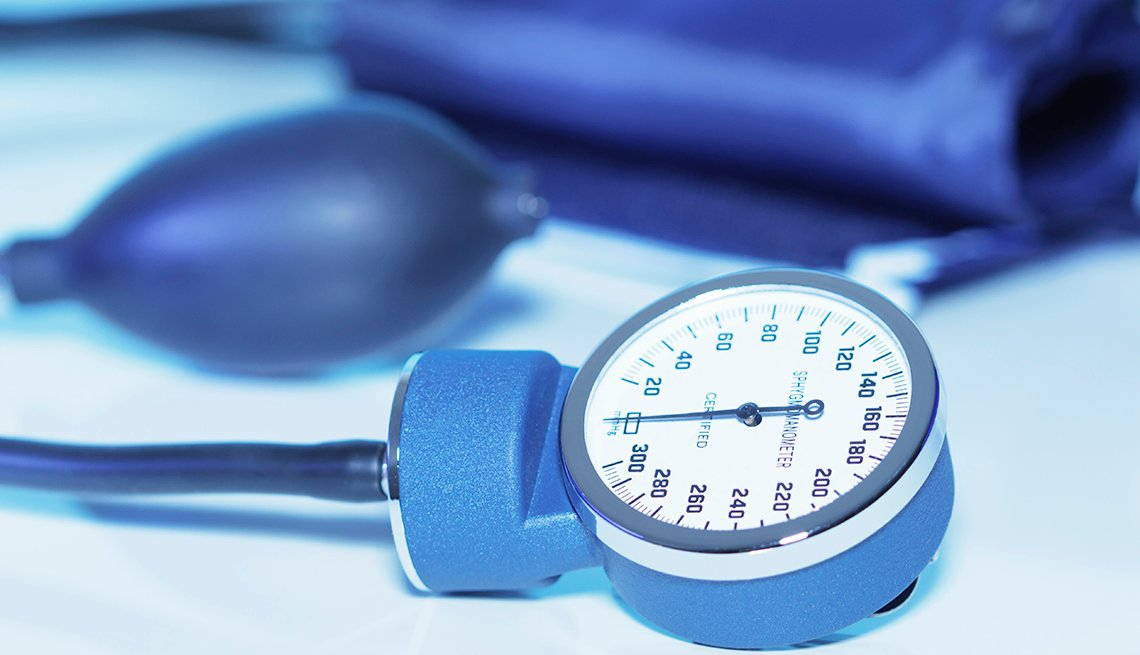 Blue mechanical blood pressure gauge on a light blue background.