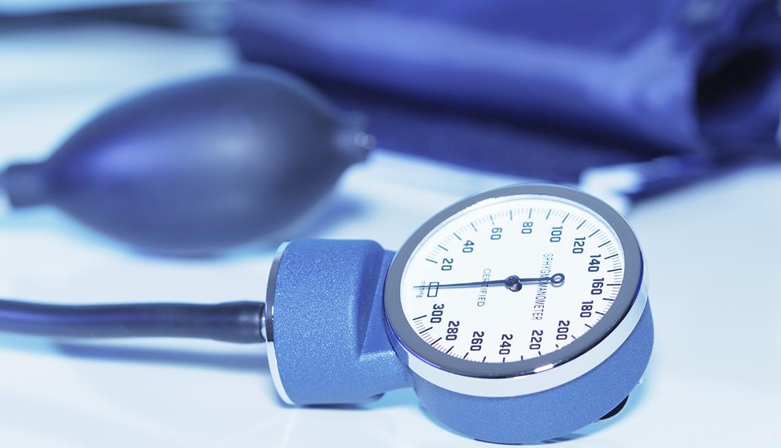 Blue mechanical blood pressure gauge on a light blue background.