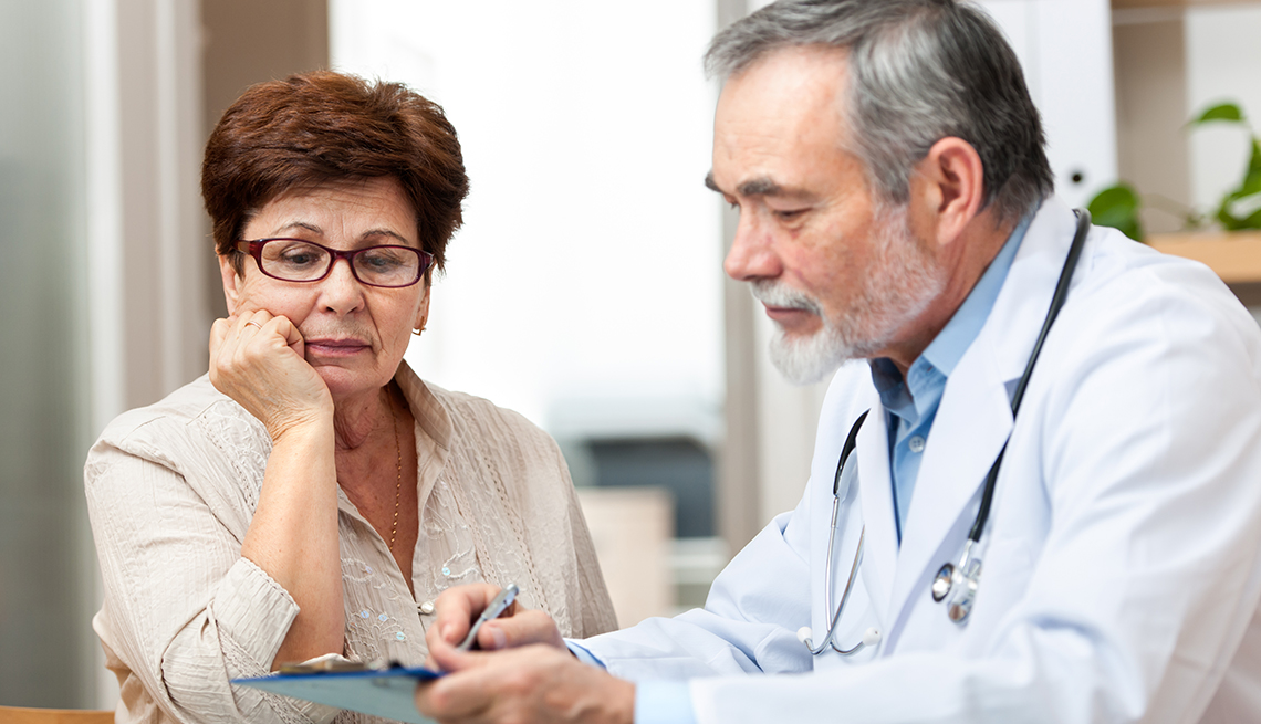 Mature female patient talking to male doctor. Patient looks confused or concerned.