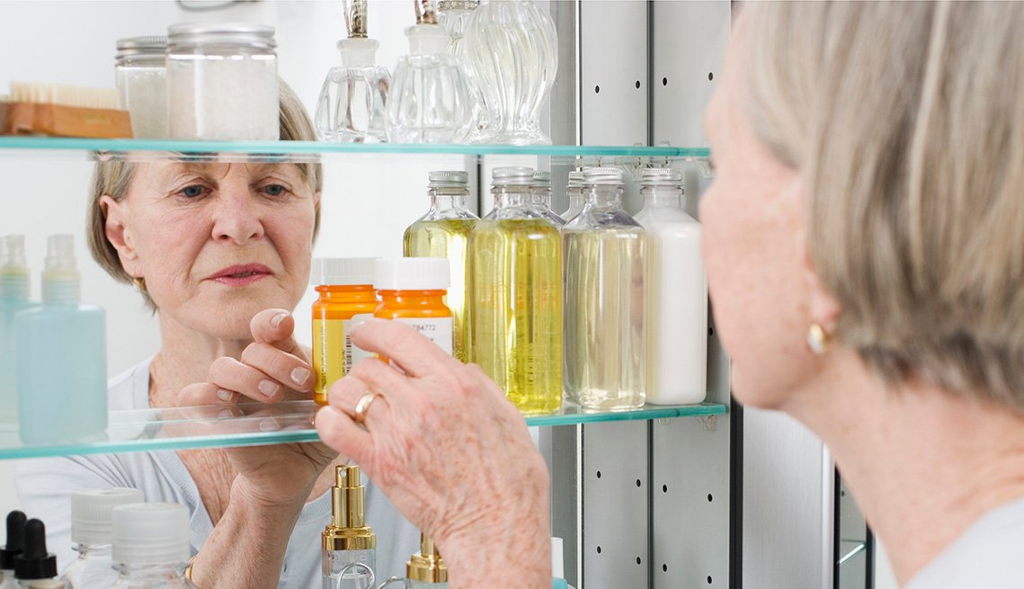 Mature woman getting pills out of a medicine cabinet. Her reflection in the mirror looks concerned.