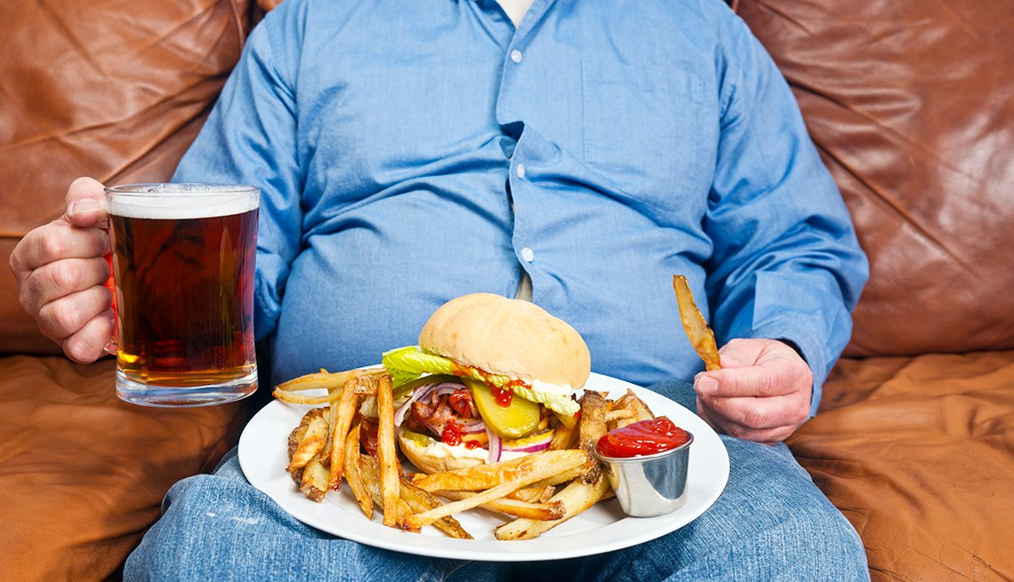 A photo of an overweight man sitting on a couch by himself, eating fast food.