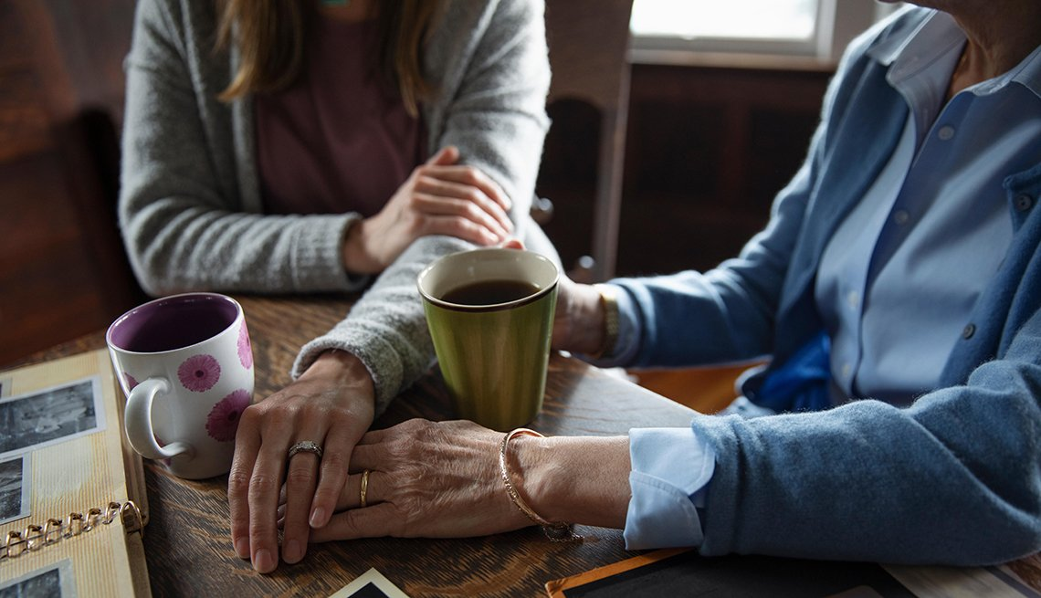 senior mother and daughter holding hands, drinking coffee and looking at photo albums