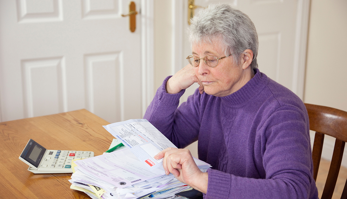 A woman sitting down and looking her stack of bills on a table