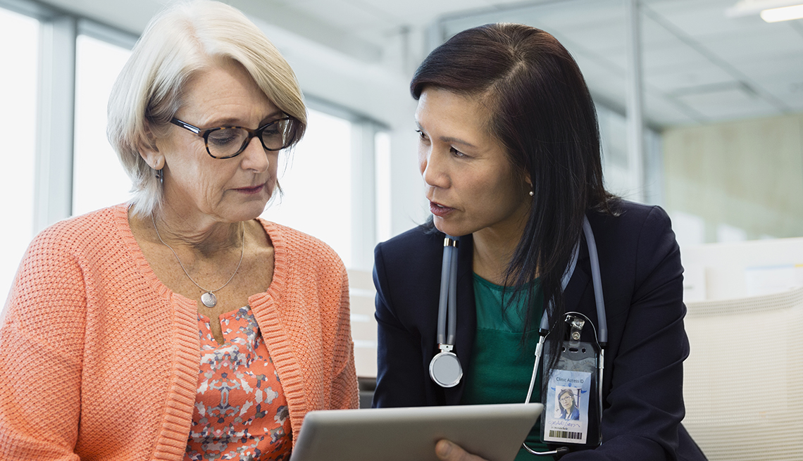 Doctor and mature patient talking and looking at a digital tablet.