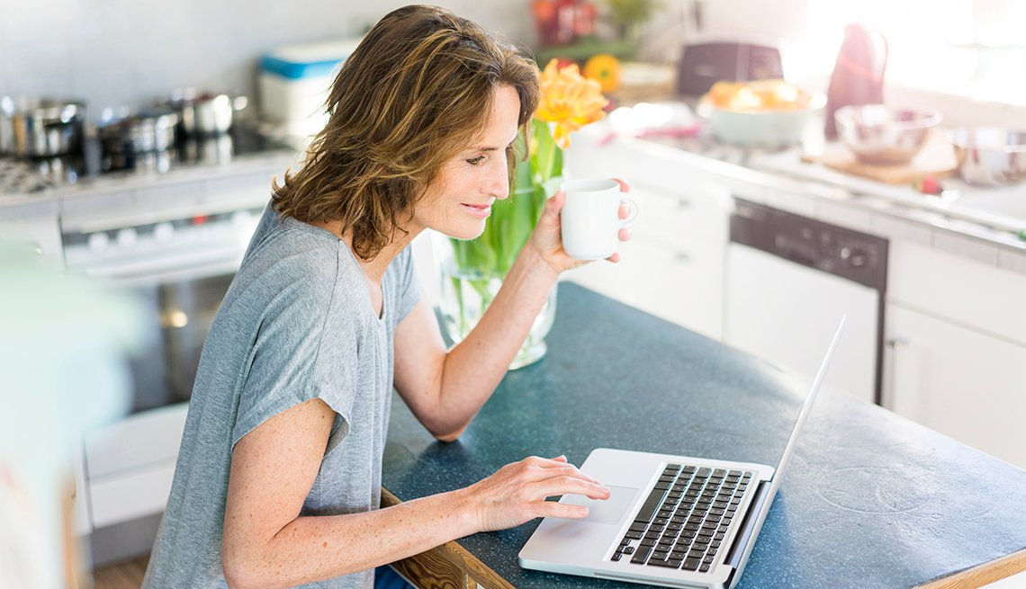 Woman reading on a laptop, drinking coffee.