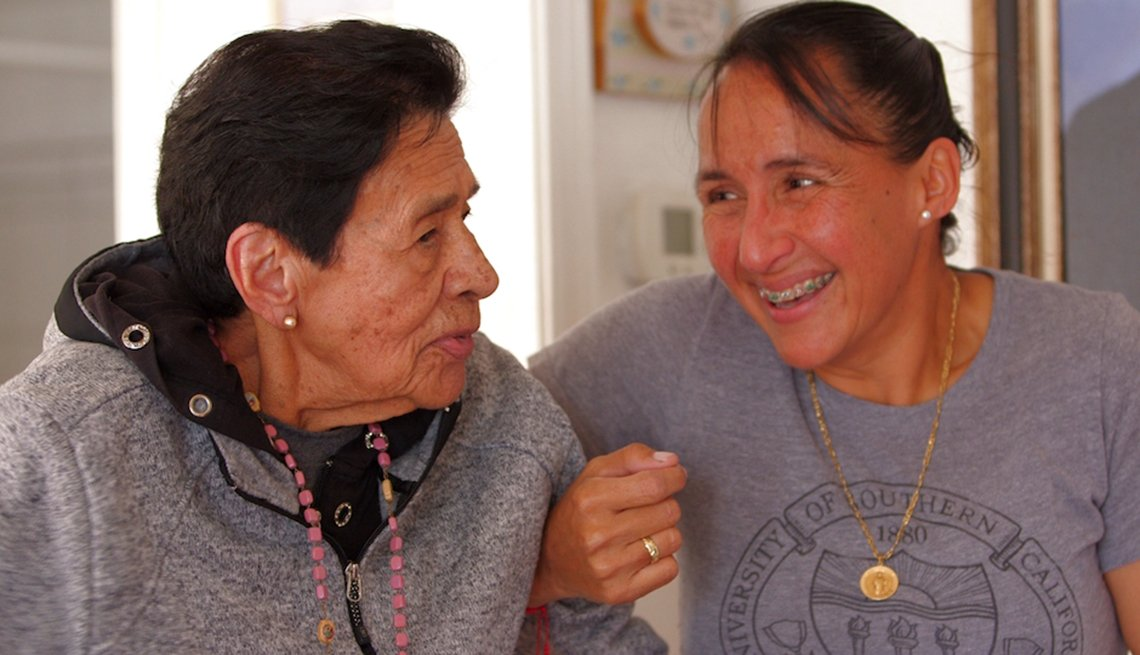 A younger woman with her arms locked with an older woman.